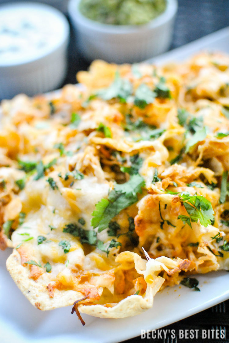 Slow Cooker Buffalo Chicken Nachos with Greek Yogurt Blue Cheese Dip & Quick Guacamole is a quick and easy appetizer or party snack! Make it into a weeknight meal by ditching the chips and serving over rice, on a pizza or in lettuce wraps. | beckysbestbites.com