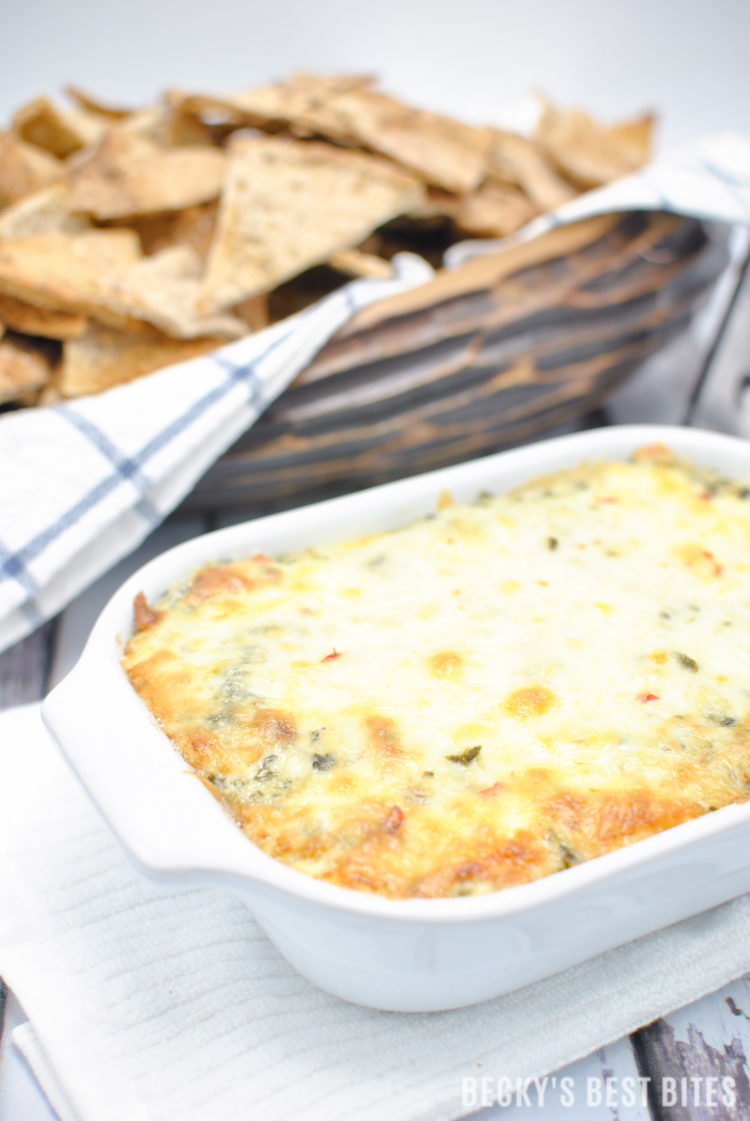Cheesy Spinach Artichoke Dip with a Kick is the perfect appetizer dip for a game day spread! No mayo, double spinach, four cheeses and just a hint of spice make this ooey gooey yumminess the best spinach artichoke dip I have ever made!! | beckysbestbites.com